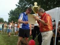A foci győztes csapatának kapitánya átveszi a díjat